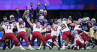 The Huskies try in vain to block a field goal attempt.