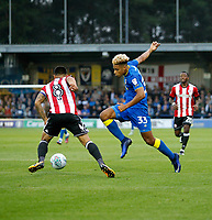 AFC Wimbledon's Lyle Taylor and Brentford's Nico Yennaris compete for the ball during the Carabao Cup match between AFC Wimbledon and Brentford at the Cherry Red Records Stadium, Kingston, England on 8 August 2017. Photo by Carlton Myrie.