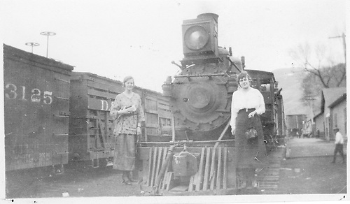 Front view of engine with two women on pilot running boards.  Train is at Cimarron depot.<br /> D&amp;RGW  Cimarron, CO