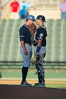 Asheville Tourists catcher Dom Nunez (9) has a chat on the mound with relief pitcher Josh Michalec (17) during the game against the Kannapolis Intimidators at Intimidators Stadium on June 28, 2015 in Kannapolis, North Carolina.  The Tourists defeated the Intimidators 6-4.  (Brian Westerholt/Four Seam Images)