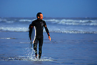 Surfer in wetsuit wading through shoreline water with surf board.