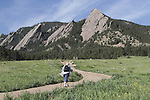 Overweight senior citizen walking uphill at Chautauqua Park with the Flatirons rock formation behind, Boulder, Colorado. .  John leads private photo tours in Boulder and throughout Colorado. Year-round.