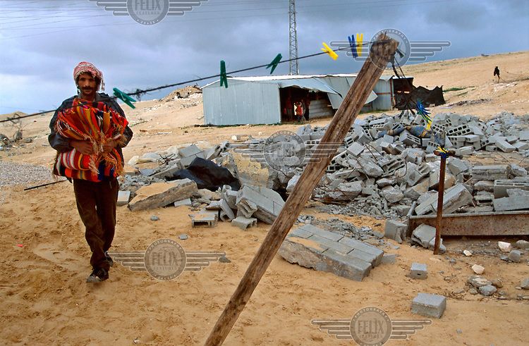 "A member of the Zanoon family walks next to the ruins of one of the five family houses demolished by Israeli authorities, in the unrecognised Bedouin village of Wadi El-Na'am..As well as the  ""usual"" problems of living in an unrecognised village (such as lack of infrastructure and regular demolition of their homes), residents of Wadi El-Na'am suffer from two added environmental nuisances.  They are directly in the path of  discharges of Bromide and other chemicals from the nearby industrial area of Ramat Hovav, causing breathing disorders among other health problems.  The village also sits under high voltage pylons."