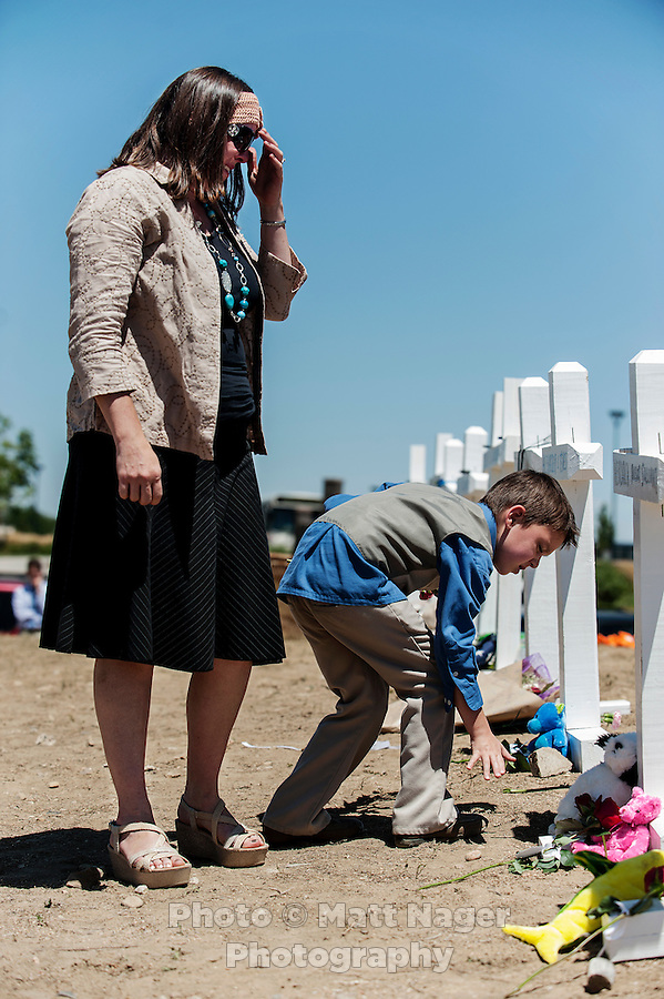 Tamara Meza (cq,left) and Isaac Meza (cq), 7, lay flowers at a shrine for the victims of the shooting at an Aurora Century 16 theater where James Holmes (cq), 24, allegedly killed 12 people and wounded many more in Aurora, Colorado, Sunday, July 22, 2012. The shootings occurred during the midnight premiere of the new Dark Knight Batman movie...Photo by MATT NAGER