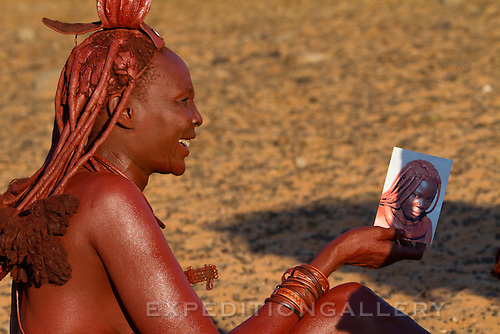 Himba woman looking at a photograph of her friend. Himba women cover their bodies with a traditional mixture of ochre and butter fat giving their skin and hair a reddish coloration. Himba are nomadic herders of goats and cattle, living in the dry desert regions of northwestern Namibia and southern Angola.