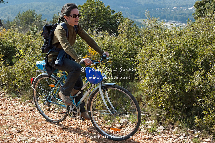 Woman Riding A Mountain Bike Alone On A Dirt Road Through The