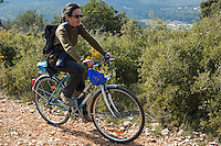 Woman riding a mountain bike alone on a dirt road through the countryside.