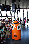 """August 01 2012, Tokyo, Japan - Visitors see and take pictures to the new robot guide """"Tawabo"""" at vantage point of Tokyo Tower. Tokyo Tower implemented the new robot guide which name is """"Tawabo"""", the first indoor robot guide in Japan. It can speak Japanese, English, Chinese and Korean, it weights 200kg and it is 160cm tall."""