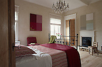In the master bedroom an old-fashioned chandelier hangs from the ceiling and the antique wrought-iron bed is covered in a mixure of old family linen and modern bedding