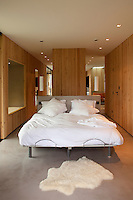 The narrow wood-clad bedroom features a modern bed with a bath in an alcove