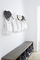 Hats and bags hanging from hooks above a wooden bench with storage compartments below.