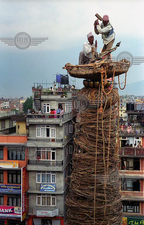 Workers risk their lives to fix the gilded adornments on the top of the huge Machendranath chariot. Rato Machendranath is a fifteen metre tall chariot with six-foot high wheels, made entirely out of wood and vines. The structure contains no nails and no pegs and is built in honour of the Hindu god Machendranath, protector of Kathmandu and bringer of rain. Each year the giant  structure is built by hand and wheeled through the streets of Patan.