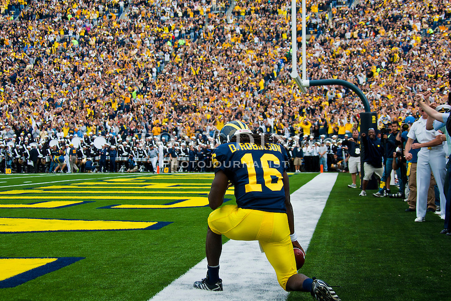 Michigan quarterback Denard Robinson (16) takes a knee in the endzone after scoring a touchdown in the first quarter of an NCAA college football game with Connecticut, Saturday, Sept. 4, 2010, in Ann Arbor, Mich. (AP Photo/Tony Ding)