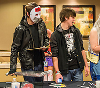 NWA Democrat-Gazette/ANTHONY REYES &bull; @NWATONYR<br /> Zach Bryant, of Rogers, dressed as Jason Voorhees, sets down his prop machete to fill out paperwork with his friend Seth Wilson of Springdale, Friday, Nov. 13, 2015 during the Arkansas Anime Festival at the Holiday Inn in Springdale. The festival continues today (Saturday) and Sunday from starting at 10 a.m. both days. The event features vendors, live demonstrations and talks about subjects including gaming, costume construction among other topics.
