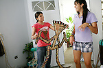 """Natalia Fernandez, 16, left, with friend Nicole Rivera, 16, right, prepares her costume for the Taino pageant, called a reinado, for the 39th annual Festival Indigena de Jayuya, which honors their Taino Indian heritage, in Jayuya, Puerto Rico, on Tuesday, November 18, 2008. Each contestant, nominated by their classmates from each school, will be judged by their costume design and native look. This year's festival is based on Taino musical instruments, and Fernandez named her costume, """"El Danzante del Sonido,"""" the sound dancer in Spanish."""