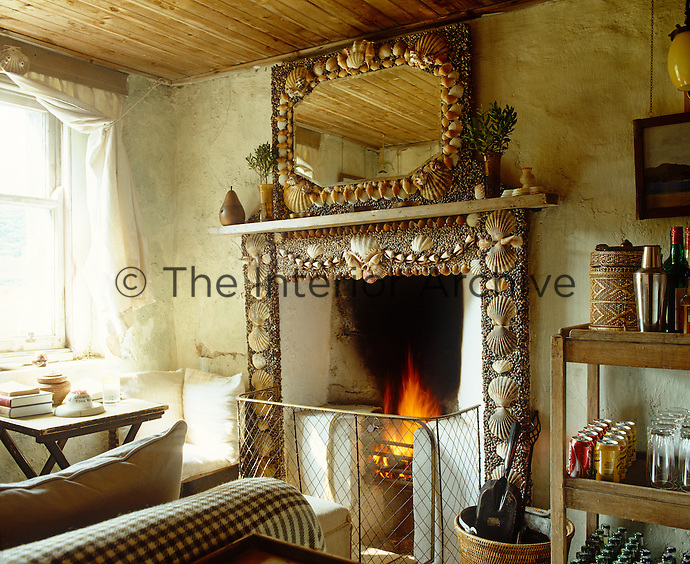 The focus of this small sitting room is a shell encrusted fireplace and mirror by Sue Jones