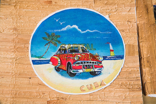 Painting of car on photo album on market stall in the Craft Market, Guardalavaca, Holguin Province, Cuba