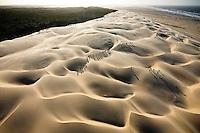 "Athletes run over sand dunes with the sea in the background near ""Barra dos Tatus"". Paulino Neves, Maranhão, Brazil, Sunday, Nov. 02, 2008."