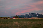 Oregon, Northeast, Enterprise. A farm scene with red barn under pink sunset skies of autumn.