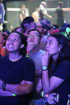 Two young women watch the video screens ecstatic as heroes battle it out in the ring<br /><br />MMA. Mixed Martial Arts &quot;Tigers of Asia&quot; cage fighting competition. Top professional male and female fighters from across Asia, Russia, Australia, Malaysia, Japan and the Philippines come together to fight. This tournament takes place in front of a ten thousand strong crowd of supporters in Pelaing Stadium. Kuala Lumpur, Malaysia. October 2015