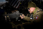 "Ted Hutton, a World War II re enactor, shooting at the Rocky Mountain Fifty Caliber Shooting Association's 2009 Machine Gun Shoot.  ..Each year the organization holds two sanctioned machine gun shoots during which machine gun owners and vendors bring their guns to shoot for a three day-long event.  Organizer Bob McBride described the muddy Fort Morgan event as ""machine gun Woodstock without the dope.""  The annual events draw shooters from around the world to shoot at propane tanks, cars filled with fuel, boxes of stick dynamite, and other ""reactive "" targets.  People wishing to own automatic firearms must be licensed by the federal government to purchase the weapon."