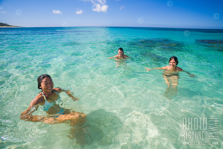 Three young women swimming in clear blue water over white sand beach at Mokuleia, North Shore of Oahu
