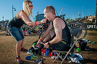 With help from his wife Shayla, Seth O'Brien puts on his cycling shoes in the Lifetime Triathalon at Tempe Town Lake, is an amputee who competes in triathalons and works a prostheticist fabricating new limbs for clients.