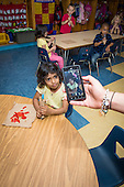 MR / Schenectady, NY. Zoller Elementary School (urban public school). Kindergarten inclusion classroom. Teacher takes photograph with camera in her smartphone of student (girl, 5) at snacktime. Student has both a healthy snack (strips of red bell peppers) and an unhealthy snack (popsicle). MR: Ram13. ID: AM-gKw. © Ellen B. Senisi.