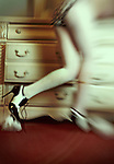 A faceless figure in polka dot panties, white stockings and black and white fetish heels rushes around a dresser, one of the drawers pulled open slightly.