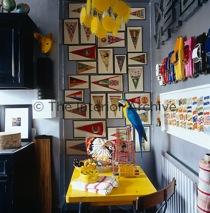 A small yellow table in a corner of this kitchen is surrounded by the memorabilia of a lifetime of collecting