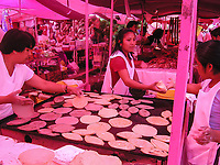 "(Mexico) – A group of women prepare food on a hot griddle by using dought oor masa. Their food stall is part of a street market. The tianguis is a popular and open-air marketplace set up on a certain day of the week in a rotating cycle at designated neighborhoods. This is done by closing off streets to vehicle traffic so that merchants (called ""ambulantes"", meaning street vendors) can set up their stalls on the on roadways. The natural pink coloration of this image is caused by sunlight filtering through the traditional plastic tarps used by sellers and vendors to protect themselves and their merchandise from the sun and rain. These markets are were set up and taken down every day of the week. This tradition of street markets in Mexico go back to pre-Columbian times. The word tianguis comes from Nahuatl, the language spoken by the Aztecs or mexicas. Photo by Eduardo Barraza ©"
