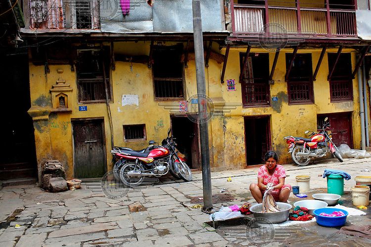 A woman washes her clothes on a street with motorcycles parked outside houses.