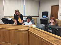 NWA Democrat-Gazette/ALEX NICOLL Washington County Election Commission Coordinator Jennifer Price (left) and members Tonya Bryant (center) and Debbie Corley (right) process and canvas Farmington ballots Tuesday night at the Washington County courthouse.