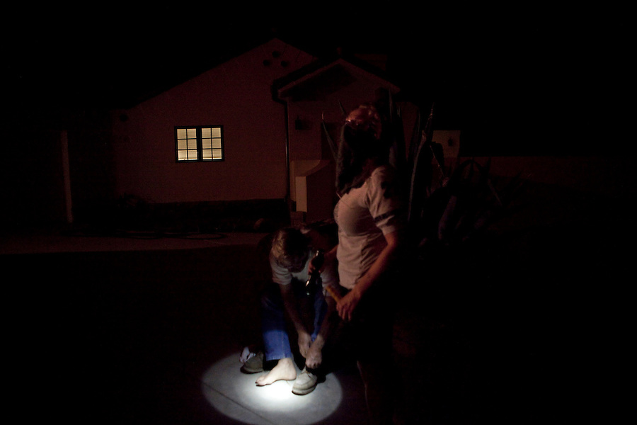Santa Barbara, Calif., May 6, 2009 - Charlie Duff puts on his shoes, while his wife Cathy Duff holds a flashlight and watches the oncoming blaze from the Jesusita Fire off of Gibraltar Road. The couple owns two homes in the area. There primary home (seen here) was nearly destroyed by last year's Tea Fire, but that blaze also knocked back the grass and brush that would be fuel for this fire. The blaze was quickly approaching their second home located higher up in the mountain. The blaze destroyed several homes in the area as well as knocking out the 220-kilovolt Goleta transmission line which are the primary source for Santa Barbara County.  Governor Arnold Schwarzenegger has declared a state of emergency. During a 10 am press conference the Governor added that 5,400 homes (13,575 people) have been evacuated, 3,500 homes are considered threatened and several dozen have been lost, though no official number has been released.
