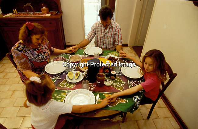RECHRIS08024.Religion. Christian. White family seated at table praying before starting dinner. All holding hands..©Per-Anders Pettersson/iAfrika Photos