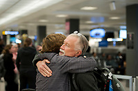 A man is embraced after arriving from Dubai on a 14-hour flight on Emirates flight 231, at the international terminal at Dulles International Airport in Dulles, Va., Monday, March16, 2020. Some people are taking the precaution of wearing face masks as they arrive to be greeted by family and or friends. Credit: Rod Lamkey / CNP/AdMedia