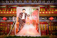 A worker from The West Lake Restaurant puts up a huge poster for the wedding reception of Zhuang Tianzhu (bridegroom) and Liu Huan (bride). Able to seat up to 5,000 people at one sitting, The West Lake Restaurant is the biggest Chinese restaurant in the world. Each week its diners, who staff are taught are 'the bringers of good fortune', devour 700 chickens, 200 snakes, 1,200 kgs of pork and 1,000 kgs of chillis. Its 300 chefs cook in five kitchens and its staff total more than 1,000.It is fully booked most nights.