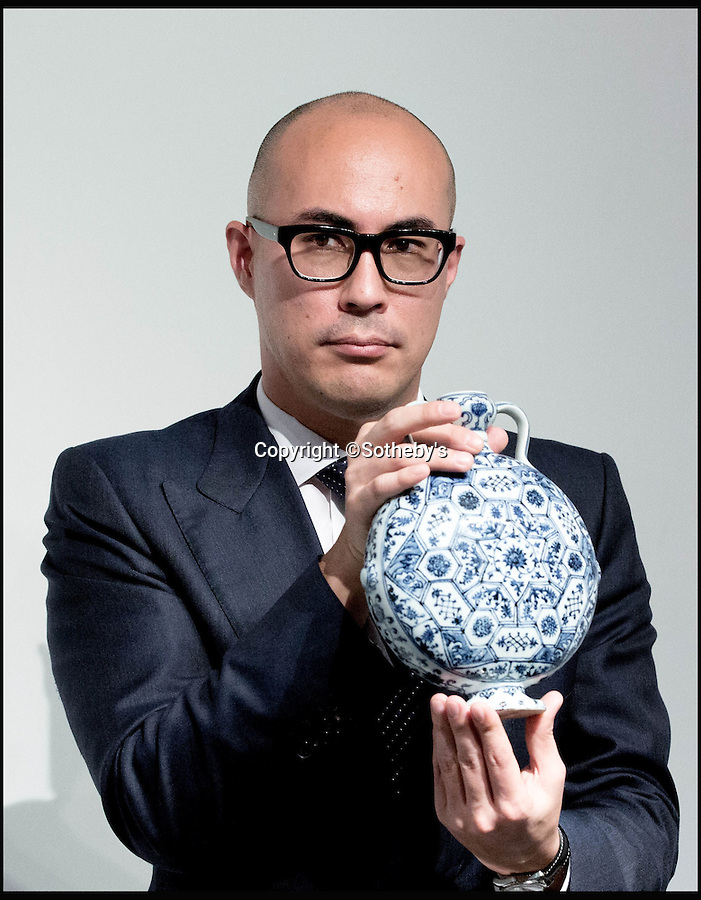 BNPS.co.uk (01202 558833)<br /> Pic: Sothebys/BNPS<br /> <br /> Dont drop it -  Nicholas Chow from Sothebys with the £10.1 million moonflask.<br /> <br /> A collection of Chinese antiques that a farmer paid as little as £100 per item for has sold for a whopping £45.9 million.<br /> <br /> The late Roger Pilkington accumulated about 100 pieces of exquisite Chinese ceramics in the late 1950s and early '60s <br /> <br /> He died in 1969 aged just 40. His 'time capsule' collection has remained in his family ever since and they have now sold it at auction.<br /> <br /> Leading the sale was a 9ins tall 15th century blue and white Moon Flask which sold for a £10.1m.