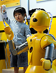 """A young visitor wears Kyokko Inc.?s flexible sensor tube (FST) body suit to remotely control Mitsubishi Heavy's Wakamaru talking robot at Robo Japan 2008 in Yokohama, Japan on Saturday 09 October 2008. Wakamaru stands at  1-meter in height and is equipped with multiple sensors and audio/visual processing functions. Defined as a """"communication robot"""" by MHI, it can have simple conversations with users while looking into their eyes and can even tell the time and play simple games, such as rock, scissors, paper."""