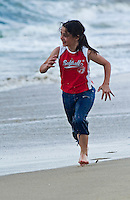 Girl (9-10) runs along beach on first visit to shore