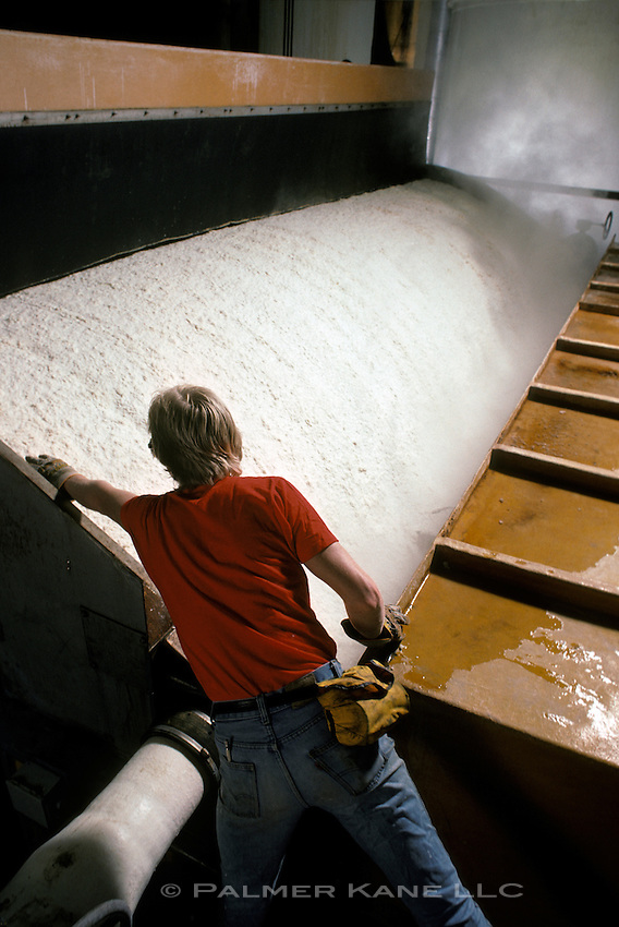 skilled workman checking slurry mixture in a paper pulp mill