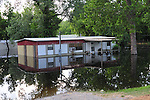 "8/13/11} Vicksburg} -- Vicksburg, MS, U.S.A. --Members of the Kings Community in Vicksburg Mississippi spend Friday The 13, 2011 checking out the rising Mississippi flood water into their homes. Robert Shiers aka Peanut paddles past his hand built cabin in the woods too check on the flood waters Friday May 13,2011 Peanuts flooded cabin on Chickasaw Road was a cabin in the woods is now a cabin on the flooded Mississippi River.  Hope and faith float as the Mississippi River continues to rise around the Kings Community on Friday the 13th of May 2011. ""Peanut "" aka Robert Shiers navigates his ""John Boat"" down Chickasaw Rd. in Vicksburg Mississippi. His hand built ,self designed cabin which sits on 14ft. stilts on the old Belle Meade Plantation was on a 5acre wheat field that is now inundated with water and only able to get to by boat.  No mail today for residents of the Kings Community in Vicksburg MS Friday May 13, 2011.The Mississippi River in Vicksburg, Mississippi is expected to crest at a record 58.5 feet. The water is moving at 2.2million cubic feet per second, to put it in perspective it would fill the SuperDome in New Orleans in 30 seconds. Pictured is the historic Yazoo Valley Railroad Station in downtown Vicksburg. The River is flooding over 1.2 million acres of farm land and damaging thousands of homes and disrupting thousands of peoples lives. Vicksburg a riverfront town steeped in war and sacrifice, gets set to battle an age-old companion: the Mississippi River. The city that fell to Ulysses S. Grant and the Union Army after a painful siege in 1863 is marshaling a modern flood-control arsenal to keep the swollen Mississippi from overwhelming its defenses. PHOTO©SUZI ALTMAN.COM.Photo by Suzi Altman."