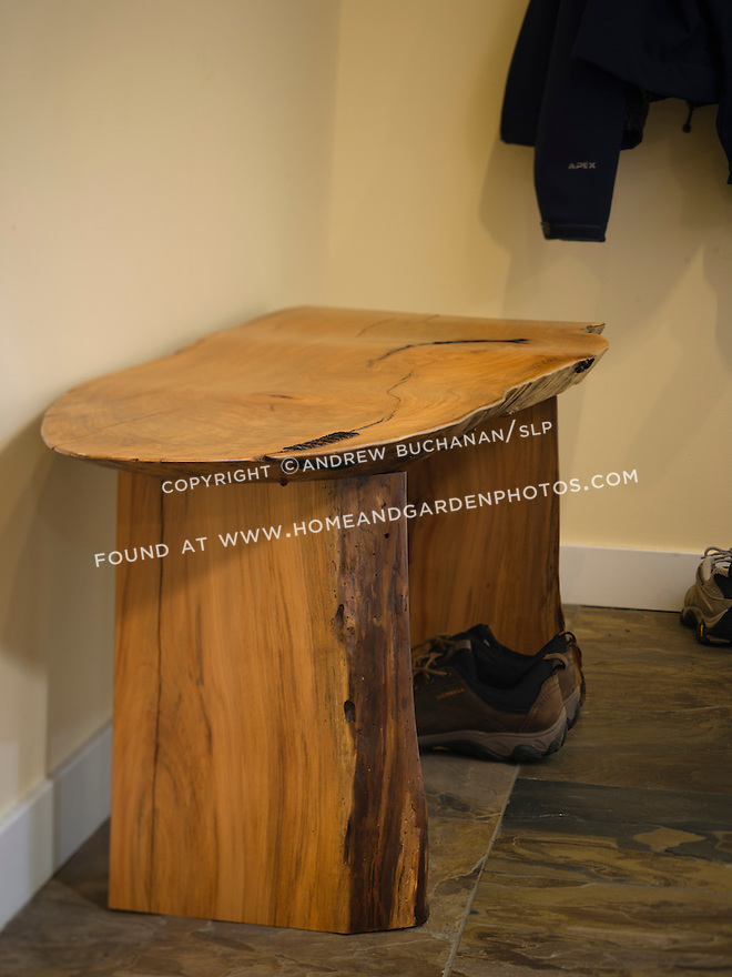 A handcrafted madrone wood bench is a focal point in the mudroom of this newly-remodeled basement. This image is available through an alternate architectural stock image agency, Collinstock located here: http://www.collinstock.com