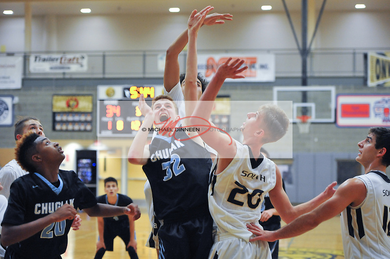 Chugiak's Kade Worley (32) drives to the hoop surrounded by South defenders Tuesday, Jan. 6, 2016.  Defending are South's Alex Adams (20) and Wyatt Babiak, and looking on is Mustang teammate Loshi Wilson.   Photo for the Star by Michael Dinneen