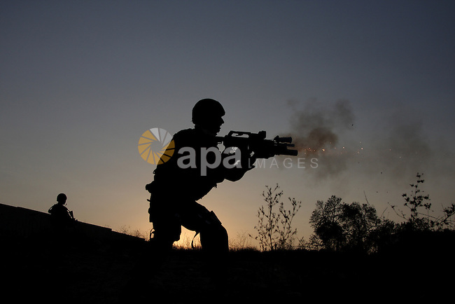 Israeli border police officers fire during during clashes with Palestinian stone-throwers at the Kalandia checkpoint between the West Bank city of Ramallah and Jerusalem, Thursday, Oct. 8, 2009. President Barack Obama's Mideast envoy finds himself increasingly hamstrung, with Israel's foreign minister on Thursday all but ruling out a peace deal for years to come and the Palestinian leader weakened by his decision not to push for a Gaza war crimes tribunal against Israel. Photo by Issam Rimawi