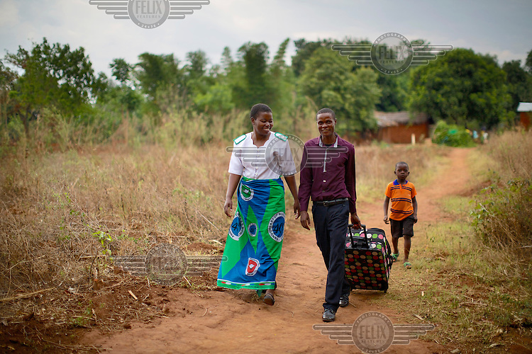 Annie Khyuza Kasaka, 36, a registered midwife/palliative care nurse at Mulanje Mission Hospital, walks with a patient's husband while on a home care visit.. Pioneering work with palliative care in rural Malawi is increasing the quality of life for thousands of people with terminal conditions including cancer, TB and arthritis-often linked to HIV infection which remains at around 10 percent of the adult population.
