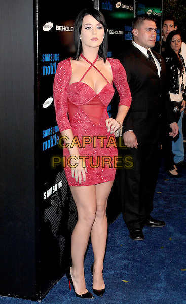 KATY PERRY .At Samsung Behold ll Premiere Launch Party  held at Boulevard 3, Hollywood, California, USA, 18th November 2009..full length mini dress red cross straps crystals sparkly hand on hip black shoes bustier patent high heels christian louboutin sleeves shrug .CAP/ADM/TC.©T. Conrad/AdMedia/Capital Pictures.
