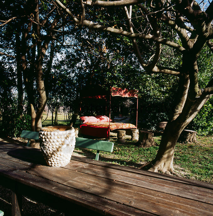 A garden scene with a wooden table and chairs. A red four poster bed with a canopy is set out on a lawn amongst trees.
