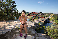 Attractive African-American athlete woman checking her email and text messages on smartphone on the 360 Bridge overlook cliff on Lake Austin, Texas.