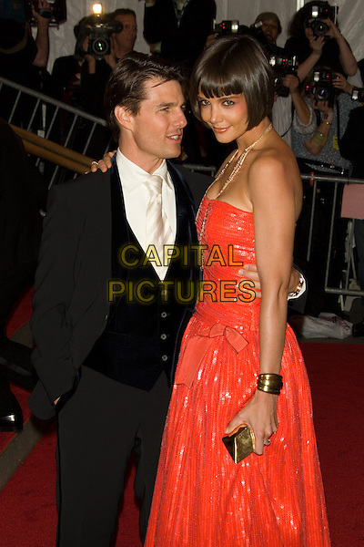 "TOM CRUISE & KATIE HOLMES.Costume Institute Gala - ""Superheroes: Fashion and Fantasy"" at The Metropolitan Museum of Art, New York, NY, USA..May 5th, 2008 .half length black suit red strapless dress gold necklace married husband wife clutch bag bracelets profile .CAP/LNC.©TOM/LNC/Capital Pictures."